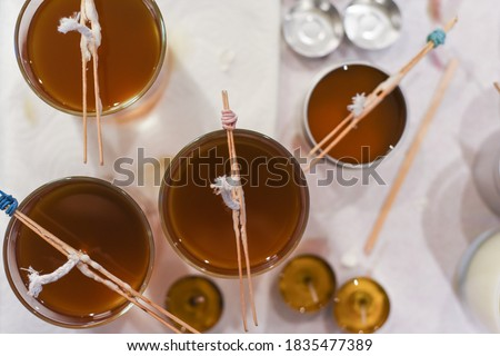 Creative occupation of candle making showing the pouring of liquid wax into jars Royalty-Free Stock Photo #1835477389