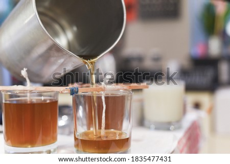 Creative occupation of candle making showing the pouring of liquid wax into jars Royalty-Free Stock Photo #1835477431