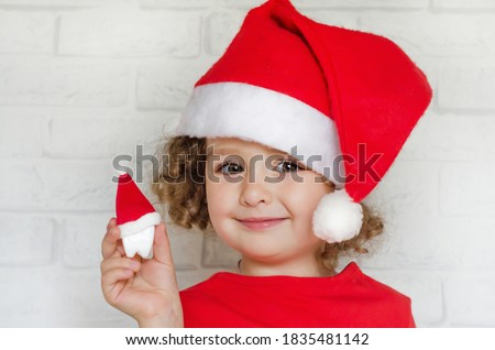 little cute beautiful girl in red santa hat holding a toy tooth. child in New Year suit smiling and looking into the camera.  dental christmas.