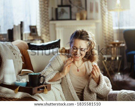 smiling young woman in knitted cosy cardigan with tray, aroma lamp, mug and pastries eating pastries at modern home in sunny autumn day. #1835581510
