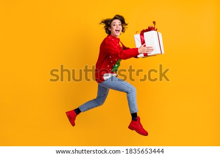 Full body profile side photo of excited girl jump run with x-mas eve noel big gift box, wear christmas tree ornament pullover sweater denim jeans isolated bright shine color background Royalty-Free Stock Photo #1835653444