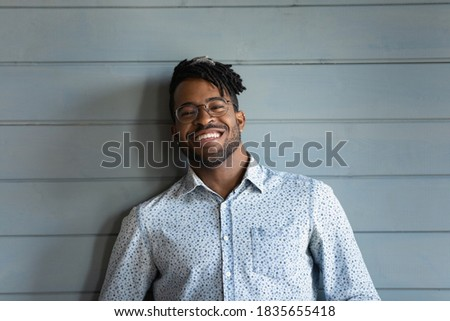 Headshot portrait of smiling young biracial man in glasses isolated on grey wooden wall background at home. Profile picture of happy 20s African American male renter in eyewear feel excited overjoyed.