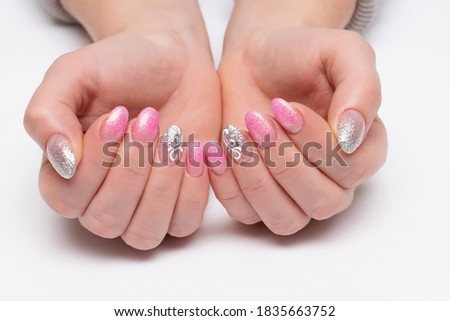 Gel nail design. Shiny pink, silver manicure with white lace, monograms, abstraction on short oval nails close-up on a white background