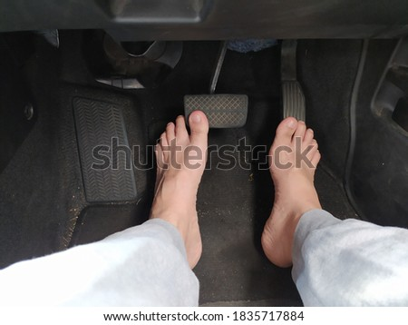 Male bare feet on the brake and accelerator pedals in a car Royalty-Free Stock Photo #1835717884