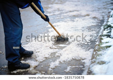 Worker breaking ice with hand ice breaker tool, cleaning ice with razor scraper on the sidewalk. Worker in uniform cleaning ice and snow with icebreaker tool. Janitor cleans area. Snow removal #1835750878