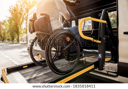 A man in a wheelchair on a lift of a vehicle for people with disabilities Royalty-Free Stock Photo #1835818411