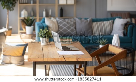 Sunlight illuminates living room workplace home office interior for comfort productive work, brown and blue colours. On wooden table laptop comfy couch with cushions on background, workday end concept Royalty-Free Stock Photo #1835827411