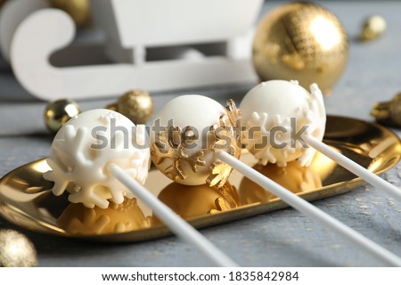 Delicious Christmas themed cake pops on golden plate, closeup Royalty-Free Stock Photo #1835842984