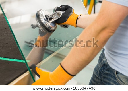 The Glazier uses a sucker for windows. Glass making workshop, The man lifts the pane of thick glass on the table with the help of specialized tools Royalty-Free Stock Photo #1835847436