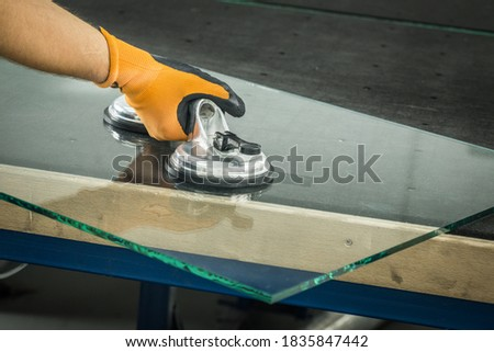 The Glazier uses a sucker for windows. Glass making workshop, The man lifts the pane of thick glass on the table with the help of specialized tools Royalty-Free Stock Photo #1835847442