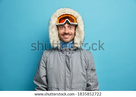 Sporty glad man enjoys winter sport recreation smiles gladfully wears ski goggles and grey jacket isolated on blue. Holidays tour recreation and traveling concept. Snowboarder leads active lifestyle Royalty-Free Stock Photo #1835852722