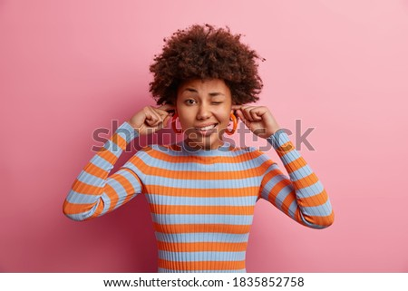 Photo of lovely curly haired young woman winks eye and plugs ears avoids hearing very loud music dressed in casual striped jumper poses against pink background. Turn sound off. Noisy atmosphere Royalty-Free Stock Photo #1835852758