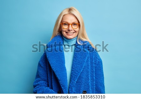 Smiling European woman with blonde hair dressed in blue winter coat has happy mood wears eyewear poses in studio. Fashionable middle aged blonde lady in outerwear going to have walk with family Royalty-Free Stock Photo #1835853310
