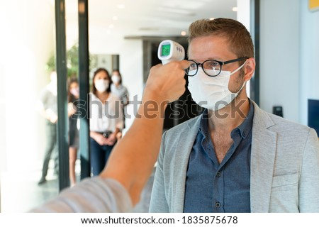 Staff check fever by digital thermometer visitor before entering the airport for scan and protect from Coronavirus Royalty-Free Stock Photo #1835875678