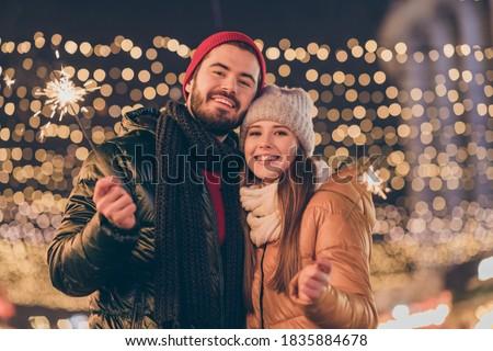Photo of positive couple enjoy celebrate christmas lights sparklers under, x-mas tradition outside illumination wear season coats #1835884678