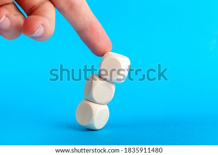 Structure collapsing, knocked over. Wooden cube tower pushed by human finger coming from above. Market collapse, crisis, lack of stability, breakdown and loss of balance abstract concept Cubes falling Royalty-Free Stock Photo #1835911480