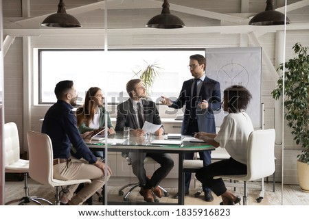 Skilled young professional business trainer in formal suit standing near flipchart, educating focused interested multiracial company managers at workshop seminar lecture event in modern office. Royalty-Free Stock Photo #1835916823