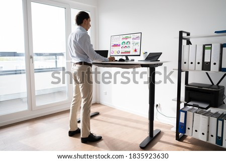 Man Working On Computer At Standing Desk In Home Office  Royalty-Free Stock Photo #1835923630
