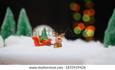 New Year's deer with a sleigh on a New Year's background. Santa Claus and deer in cartoon style. Sled with New Year's gifts.