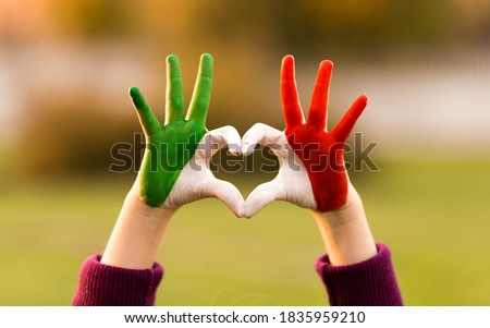 Heart shape of kids hand painted in italy flag colors, kids body language, childrens love concept. Heart hand on nature sunset bokeh background