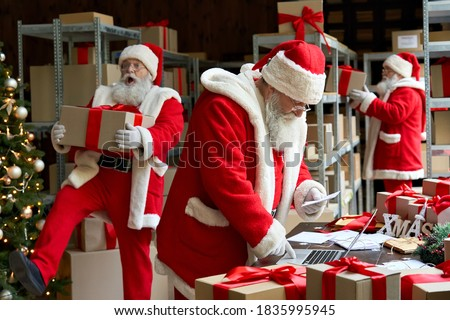 Many busy Santa Clauses packing gift boxes preparing fast xmas delivery. Three funny Santas walking in workshop warehouse in Merry Christmas rush delivering presents during holiday preparations. #1835995945