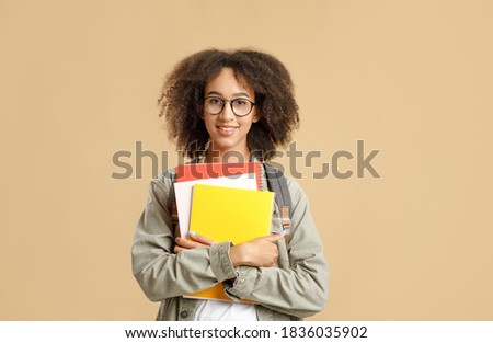 Modern student, smart and nerdy pupil after quarantine. Smiling african american young woman with glasses and backpack hugs her notebooks and looks at camera, isolated on yellow background, copy space