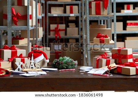Decorated Merry Christmas table with gifts boxes in warehouse interior background. Many presents wrapped with red ribbons and letters on desk in storage. Xmas postal shipping delivery concept. #1836061498