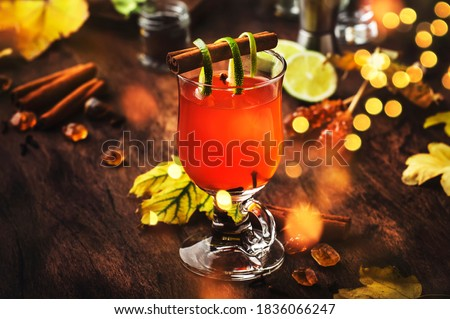 Hot rum punch, grog, autumn or winter warming alcoholic cocktail with dark rum, port, honey, lime juice, black tea, cinnamon and cloves in tall glass, golden bokeh lights Royalty-Free Stock Photo #1836066247