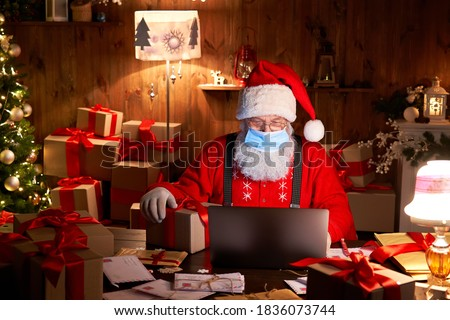 Old bearded Santa Claus wearing face mask, holding gift box on xmas eve sitting at cozy home table late in night using laptop computer. Merry Christmas Covid 19 coronavirus social distance concept. #1836073744
