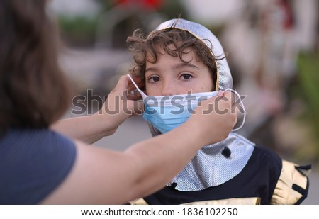 Close up of a mother putting a face mask on a young boy in a Halloween costume for safety and protection during trick or treating.