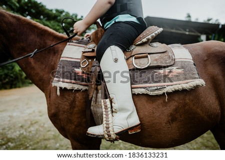 Kids learn to ride a horse.Happy asian kid girl riding horse in horse school farm club with leather boots Horseback riding, lovely powerful equestrian.Cowgirl kid fun in farm.