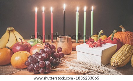 Kwanzaa holiday concept with decorate seven candles red, black and green, gift box, pumpkin,corn and fruit on wooden desk and black background. vintage effect
