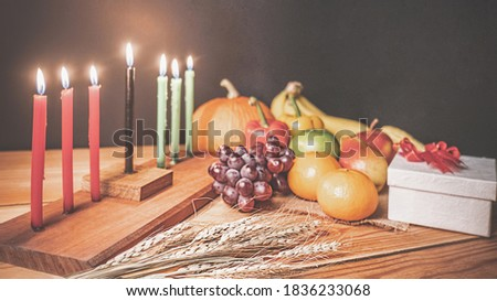 Kwanzaa holiday concept with decorate seven candles red, black and green, gift box, pumpkin,corn and fruit on wooden desk and black background.vintage effect