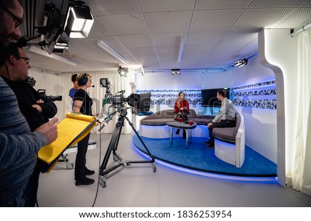 A TV show being filmed in a studio. The presenters are sitting on the studio sofa and talking to each other while the camera crew films them with film cameras. #1836253954