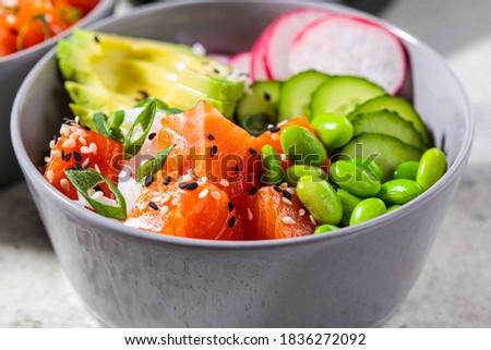 Poke bowl with salmon, rice, avocado, edamame beans, cucumber and radish in a gray bowl. Hawaiian ahi poke bowl, gray background. Royalty-Free Stock Photo #1836272092