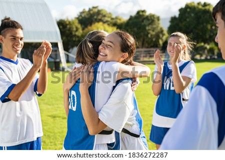 Happy football players hugging on field after scoring a goal. Soccer teammates embracing while players clapping hands on victory. Successful girl soccer players celebrating after winning the match. Royalty-Free Stock Photo #1836272287