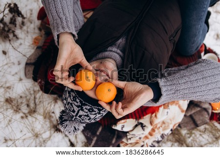 The man lies in the snow and smiles broadly. The man's eyes are closed with tangerines. High quality photo