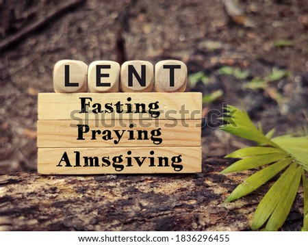 Lent Season,Holy Week and Good Friday concepts - words lent fasting praying almsgiving on wooden blocks in vintage background. Stock photo.