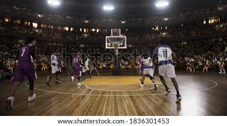 Basketball players on big professional arena during the game. Tense moment of the game. Stadium and crowd are made in 3d.