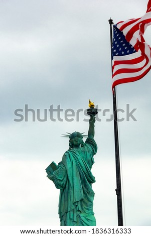 The Statue of Liberty on Liberty Island and the waving USA flag in a blue sky. The view of gorgeous Statue of Liberty and USA flag in Manhattan, New York.
