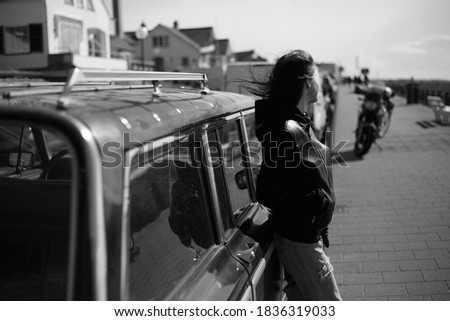 Black and white photo outside. Back view of a hipster girl with hair blowing.