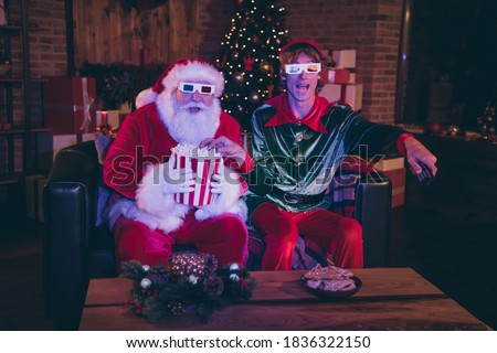 Photo portrait of santa claus and elf eating popcorn using remote watching movie on sofa in 3d glasses #1836322150