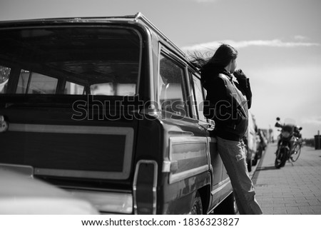 Frame view. Black and white photo outside. Back view of a hipster girl with hair blowing.