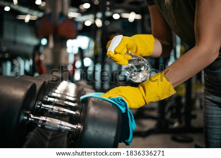 Young female worker disinfecting cleaning and weeping expensive fitness gym equipment with alcohol sprayer and cloth. Coronavirus global world pandemic and health protection safety measures. Royalty-Free Stock Photo #1836336271