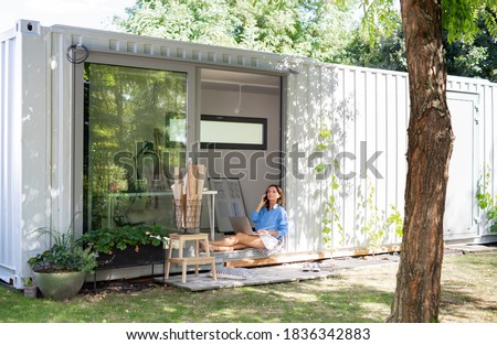 Mature woman working in home office in container house in backyard. Royalty-Free Stock Photo #1836342883