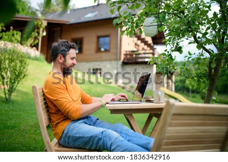 Side view of man with laptop working outdoors in garden, home office concept. Royalty-Free Stock Photo #1836342916