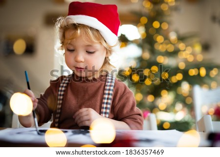 Portrait of small girl indoors at home at Christmas, painting pictures.