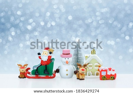 Santa Claus doll and Christmas decorations on snowing background, creative artwork Christmas and new year decoration