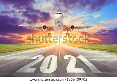 The inscription on the runway 2021 surface of the airport runway with take off airplane. Concept of travel in the new year, holidays Royalty-Free Stock Photo #1836439702