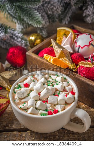 Hot chocolate with marshmallows, warm chocolate drink for Christmas morning breakfast, on wooden background with Christmas decorations, cozy winter pic copy space